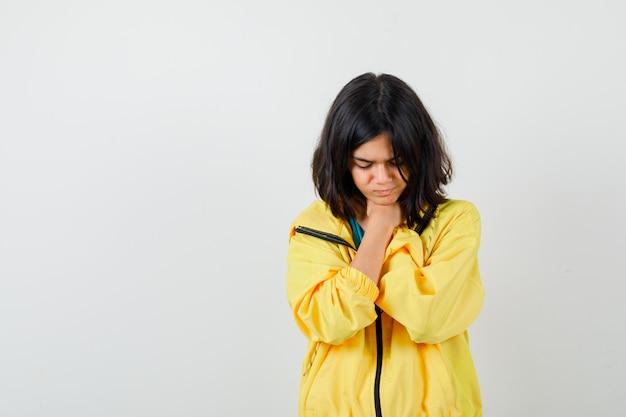 Tienermeisje in gele jas die lijdt aan keelpijn en boos kijkt, vooraanzicht.