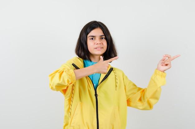 Tienermeisje in gele jas die naar rechts wijst en er vrolijk uitziet, vooraanzicht.
