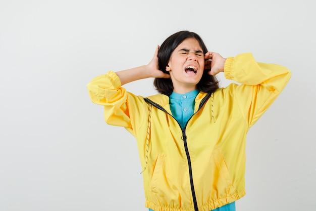 Tienermeisje in gele jas die schreeuwt terwijl ze zich klaarmaakt om het hoofd met handen vast te klemmen en er treurig uitziet, vooraanzicht.