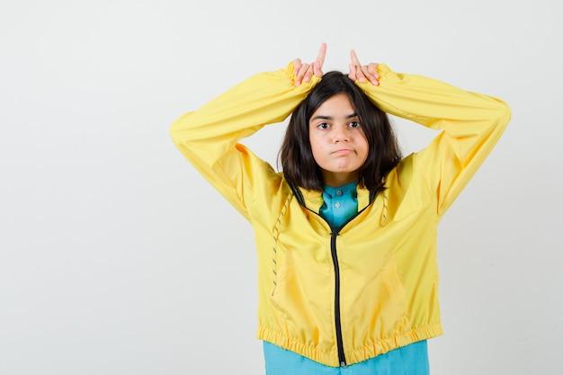 Tienermeisje in gele jas die vingers boven het hoofd houdt als stierenhoorns en er ontevreden uitziet, vooraanzicht.