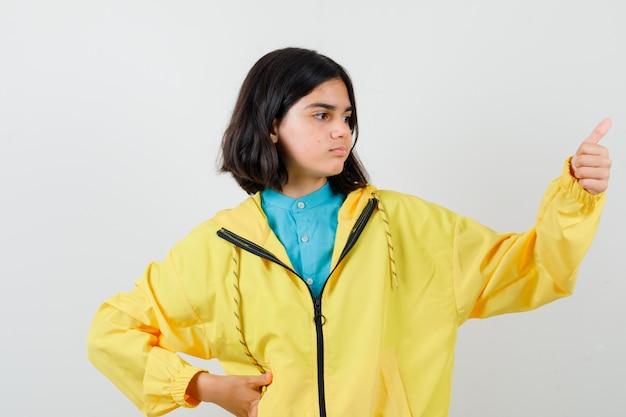 Tienermeisje in gele jas duim opdagen en tevreden kijken, vooraanzicht.