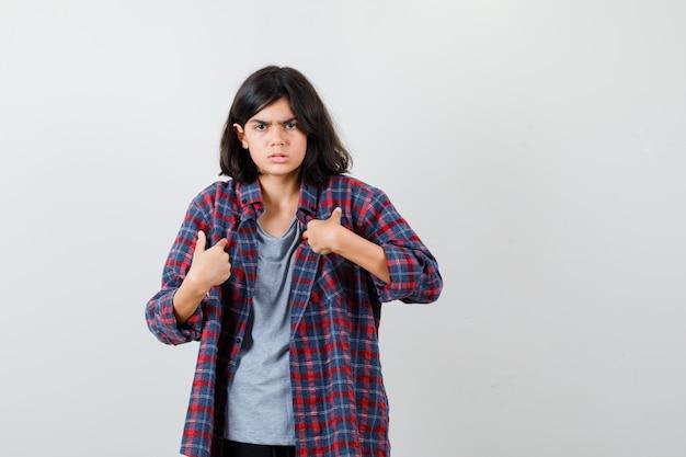 Tienermeisje in geruit overhemd dat naar zichzelf wijst en weemoedig kijkt, vooraanzicht.