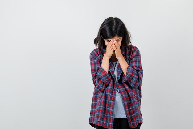 Tienermeisje in geruit overhemd hand in hand op haar gezicht en kijkt boos, vooraanzicht.