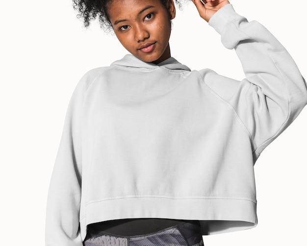 Tienermeisje in grijze hoodie voor street fashion fotoshoot