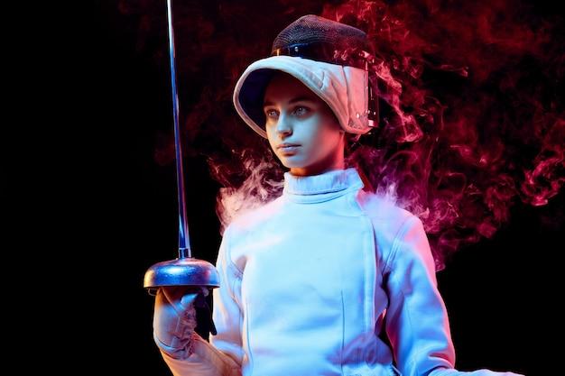 Tienermeisje in hekwerkkostuum met in hand zwaard dat op zwarte muur wordt geïsoleerd