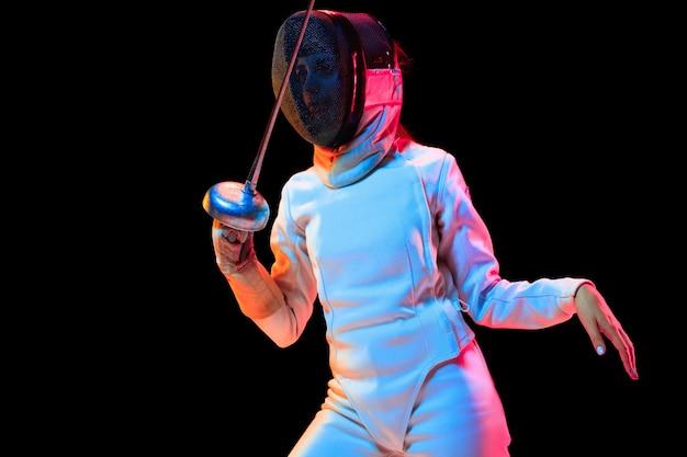 Tienermeisje in hekwerkkostuum met in hand zwaard geïsoleerd op zwarte achtergrond, neonlicht.