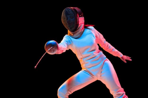 Tienermeisje in hekwerkkostuum met in hand zwaard geïsoleerd op zwarte achtergrond, neonlicht. Gratis Foto