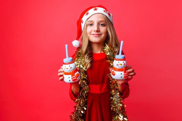 Tienermeisje in kerstmanhoed en klatergoud op de hals