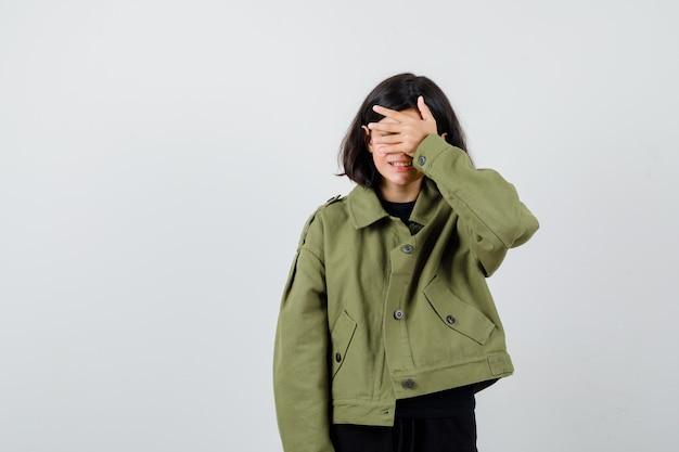 Tienermeisje in legergroen jasje dat de hand op de ogen houdt en er opgewonden uitziet, vooraanzicht.