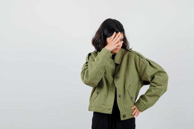 Tienermeisje in legergroen jasje dat gezicht achter hand verbergt en depressief kijkt, vooraanzicht.