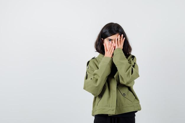 Tienermeisje in legergroen jasje dat handen op het gezicht houdt en er ingetogen uitziet, vooraanzicht.