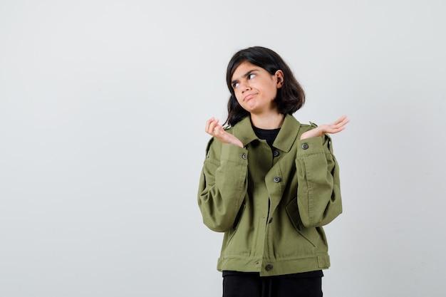 Tienermeisje in legergroen jasje dat hulpeloos gebaar toont, opzij kijkt en ontevreden kijkt, vooraanzicht.