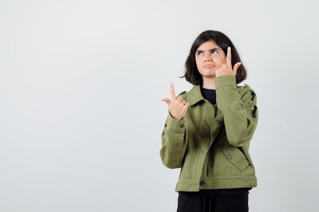 Tienermeisje in legergroen jasje dat omhoog wijst, omhoog kijkt en peinzend kijkt, vooraanzicht.