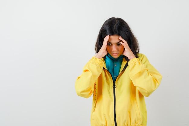 Tienermeisje in overhemd, gele jas die over haar slapen wrijft en er gestrest uitziet, vooraanzicht.