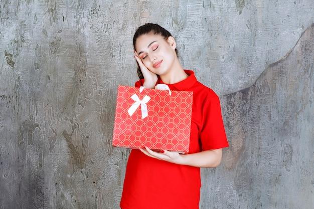 Tienermeisje in rood shirt met een rode boodschappentas en ziet er moe en slaperig uit.