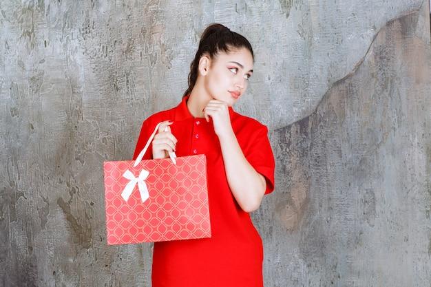 Tienermeisje in rood shirt met een rode boodschappentas en ziet er verward en attent uit.