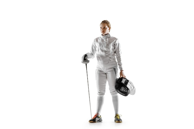 Tienermeisje in schermend kostuum met in hand zwaard dat op witte achtergrond wordt geïsoleerd. jong vrouwelijk kaukasisch model in beweging, actie