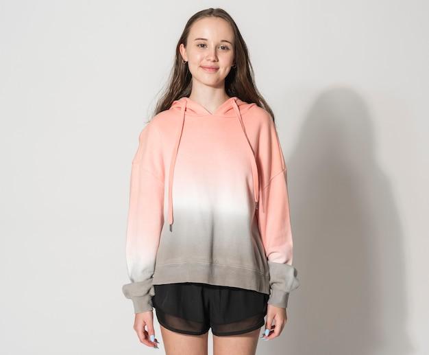 Tienermeisje in slay the day oranje hoodie voor street fashion fotoshoot