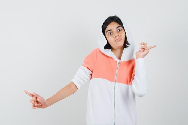 Tienermeisje in sweatshirt dat achteruit wijst en voorzichtig kijkt.