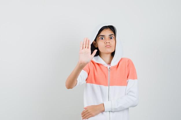 Tienermeisje in sweatshirt dat stopgebaar toont en aandachtig kijkt.