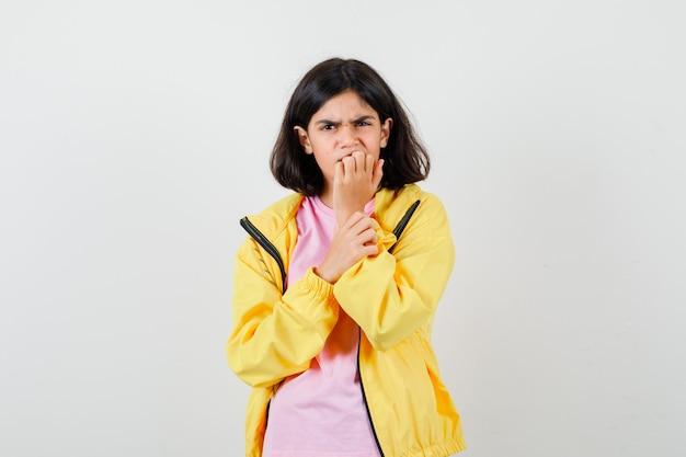 Tienermeisje in t-shirt, gele jas die nagels bijt en er gestrest uitziet, vooraanzicht.