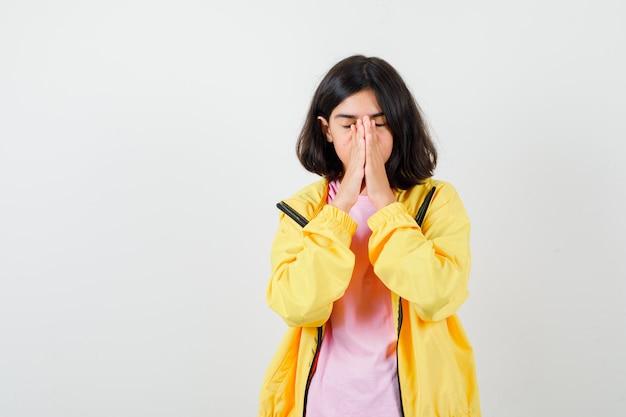 Tienermeisje in t-shirt, gele jas hand in hand in biddend gebaar en gefocust, vooraanzicht.