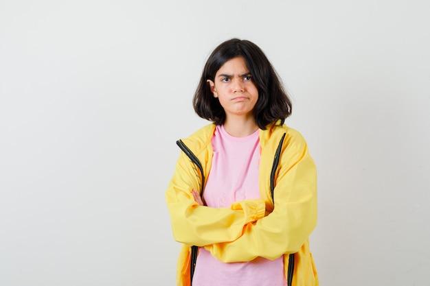 Tienermeisje in t-shirt, gele jas met armen gevouwen en boos, vooraanzicht.