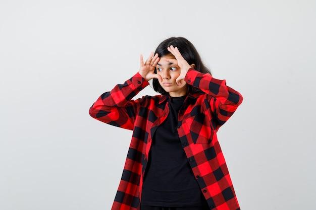 Tienermeisje in t-shirt, geruit hemd dat ogen opent met vingers en voorzichtig kijkt, vooraanzicht.