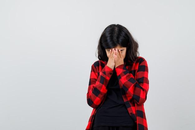 Tienermeisje in t-shirt, geruit hemd hand in hand op gezicht en bedroefd, vooraanzicht.