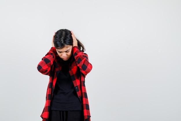 Tienermeisje in t-shirt, geruit hemd hand in hand op oren en verveeld, vooraanzicht.