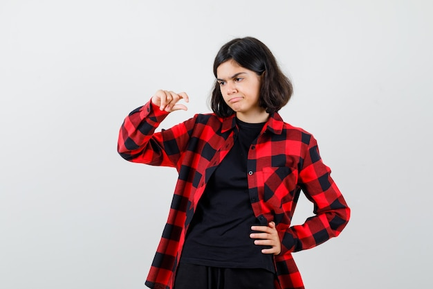 Tienermeisje in t-shirt, geruit hemd met een klein bordje en ziet er ontevreden uit, vooraanzicht.