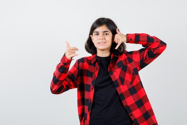 Tienermeisje in t-shirt, geruit hemd met telefoongebaar en vrolijk, vooraanzicht.