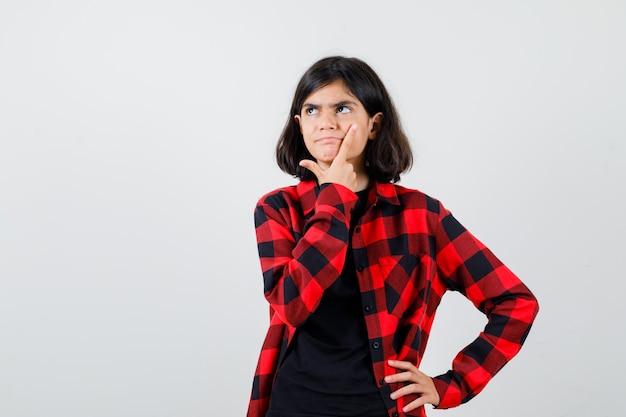 Tienermeisje in t-shirt, geruit hemd staat in denkende pose en kijkt peinzend, vooraanzicht.