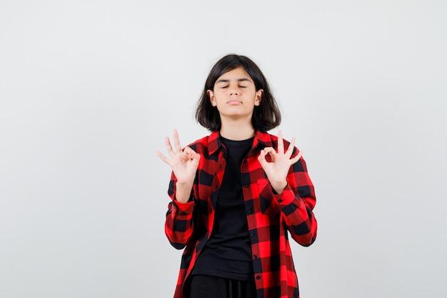 Tienermeisje in t-shirt, geruit overhemd dat een goed gebaar toont en er ontspannen uitziet, vooraanzicht.