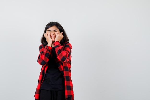 Tienermeisje in t-shirt, geruit overhemd dat gezicht op haar handen dempt en er grappig uitziet, vooraanzicht.