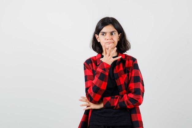 Tienermeisje in t-shirt, geruit overhemd dat handen in de buurt van gezicht opheft en peinzend, vooraanzicht kijkt.