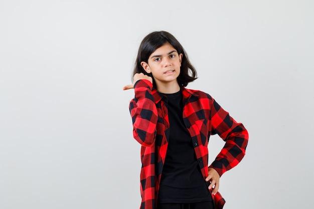 Tienermeisje in t-shirt, geruit overhemd dat met duim naar de linkerkant wijst en er vrolijk uitziet, vooraanzicht.