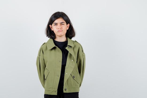 Tienermeisje in t-shirt, groen jasje dat één oog sluit terwijl ze de lippen buigt, handen achter de rug vasthoudt en ontevreden kijkt, vooraanzicht.