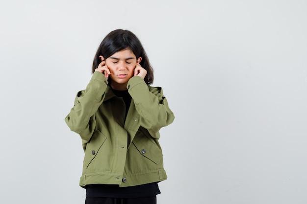 Tienermeisje in t-shirt, groen jasje dat oren stopt met vingers en er gestrest uitziet, vooraanzicht.