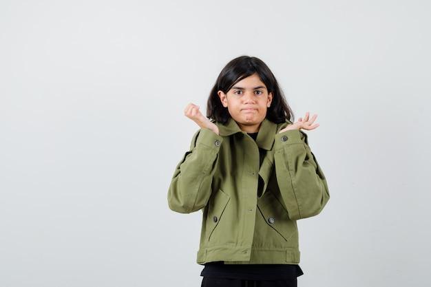 Tienermeisje in t-shirt, jas die twijfelgebaar toont en besluiteloos kijkt, vooraanzicht.