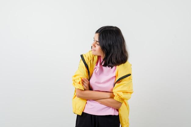 Tienermeisje in t-shirt, jas met armen gevouwen, opzij kijkend en nieuwsgierig, vooraanzicht.