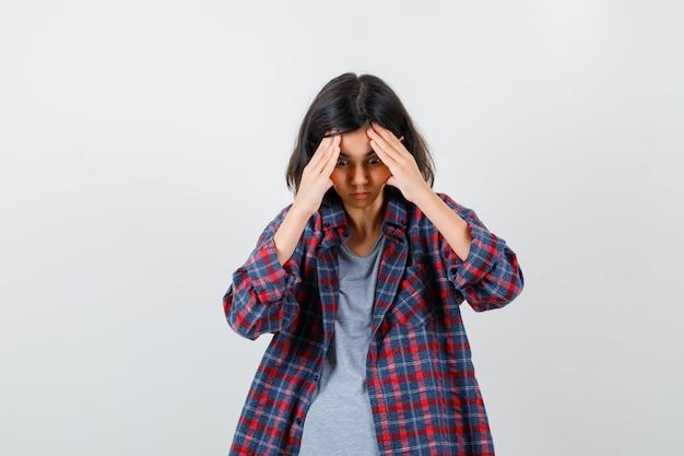 Tienermeisje in vrijetijdskleding die handen boven het hoofd houdt, naar beneden kijkt en geïrriteerd kijkt, vooraanzicht.