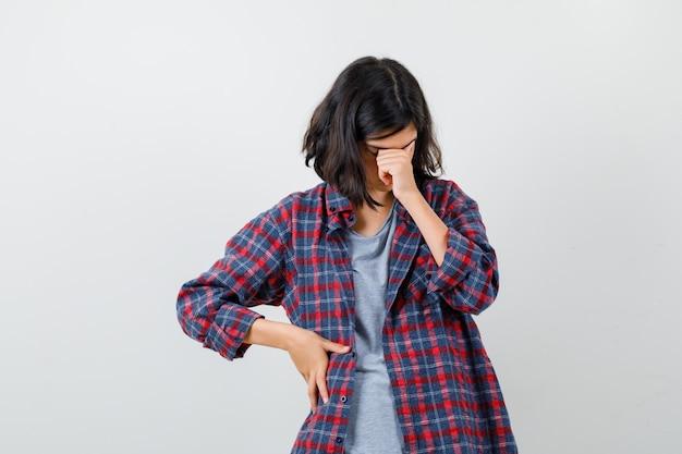 Tienermeisje in vrijetijdskleding die hoofd naar beneden buigt, ogen en neus wrijft en er depressief uitziet, vooraanzicht.