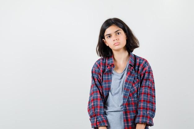 Tienermeisje in vrijetijdskleding en ziet er somber uit, vooraanzicht.