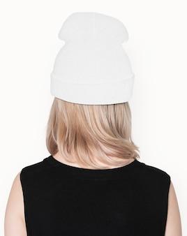 Tienermeisje in witte muts openhartig voor street fashion shoot achteraanzicht