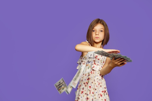 Tienermeisje in zomerjurk staande geïsoleerd met amerikaanse dollar geldbankbiljetten over fluweel