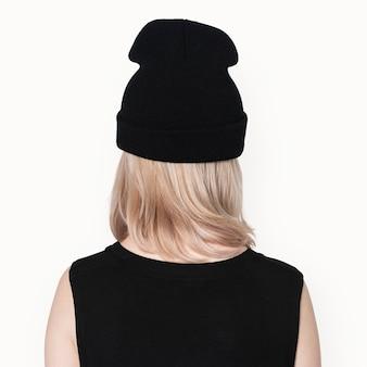 Tienermeisje in zwarte muts openhartig voor street fashion shoot achteraanzicht
