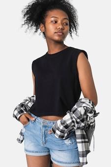 Tienermeisje in zwarte top en flanellen shirt voor jeugdkleding grunge fashion shoot