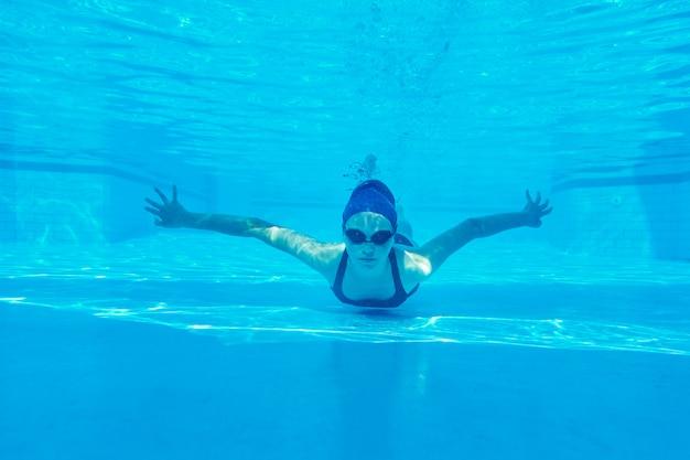 Tienermeisje in zwempak met beschermende brillen en zwemmuts zwemmen onderwater in pool