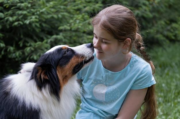 Tienermeisje kijken naar australische herdershond. huisdieren zorgconcept. liefde en vriendschap
